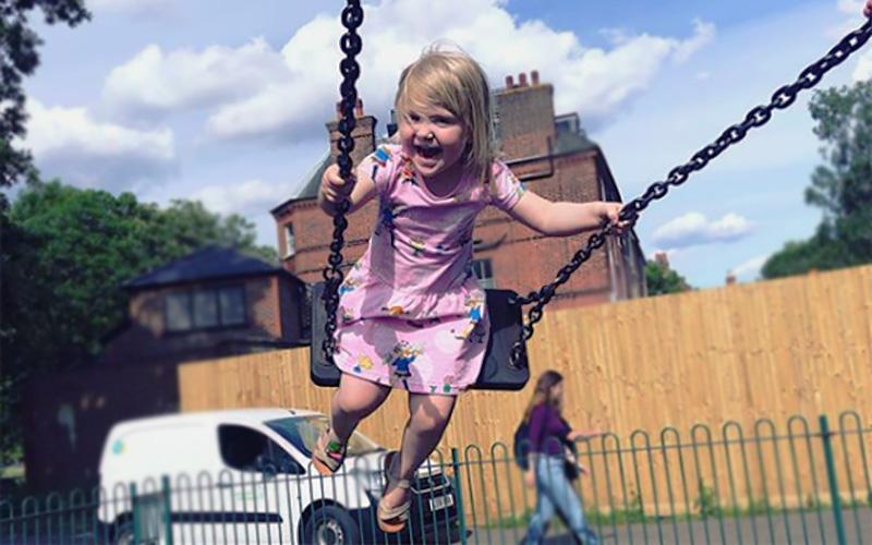 Poppy, who has SDS, swings outside on a swingset